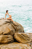 Beautiful girl in blue swimsuit sit on big stone. Royalty Free Stock Image