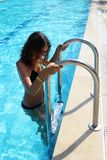 Beautiful girl in blue swimsuit and sun glasses is looking at camera and smiling while standing on ladder of the pool royalty free stock photography