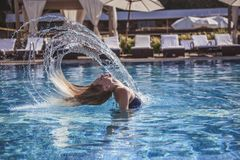 Girl at the pool. Beautiful girl in blue swimsuit is throwing her wet hair back while swimming in the pool Stock Images
