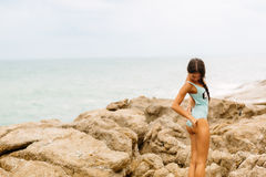 Beautiful girl in blue swimsuit walk on big stone. Royalty Free Stock Photos