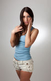 A beautiful girl in a blue t-shirt with a gray bac Royalty Free Stock Image