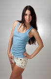 A beautiful girl in a blue t-shirt with a gray bac Stock Photos