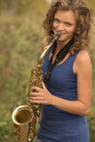 Beautiful girl in a blue t-shirt playing the saxophone in gold o Royalty Free Stock Photos