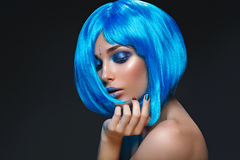 Beautiful girl in blue wig. Beautiful young woman with glowing skin, fashion make-up and metallic nails in short blue wig touching hair. Beauty shot on black Stock Image