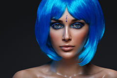 Beautiful girl in blue wig. Beautiful young woman with glowing skin, fashion smokey make-up in short blue hair wig. Beauty shot on black background. Copy space Stock Image
