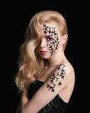 Beautiful girl with body-art mask. On her face and body.Young beautiful woman over black background royalty free stock images