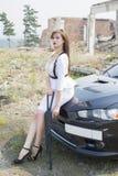 Beautiful girl bodyguard next to a sports car. Royalty Free Stock Photos
