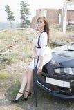 Beautiful girl bodyguard next to a sports car. Stock Image