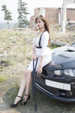 Beautiful girl bodyguard next to a sports car. Royalty Free Stock Photography