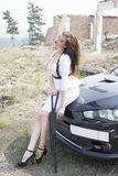 Beautiful girl bodyguard next to a sports car. Royalty Free Stock Images