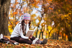 Beautiful girl with book in the autumn park stock photography