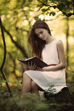 Beautiful girl with book in the forest Stock Images
