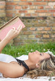Beautiful girl with book on the grass royalty free stock photos
