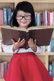 Beautiful girl with book in library Stock Images