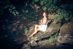 Girl with book onbank of small river Royalty Free Stock Images