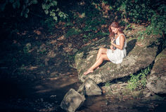 Girl with book onbank of small river Royalty Free Stock Image