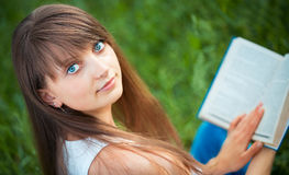 Beautiful girl with book in the park on green grass Royalty Free Stock Images