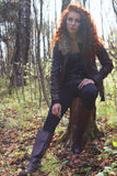 Beautiful girl in boots and jacket poses on tree stump Royalty Free Stock Photos