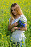 Beautiful girl with bouquet of cornflowers on flowering rapeseed Royalty Free Stock Photos