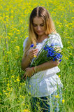 Beautiful girl with bouquet of cornflowers on rapeseed field Stock Photos