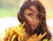 Beautiful girl with a bouquet of maple leaves Stock Images