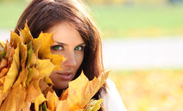 Beautiful girl with a bouquet of maple leaves Stock Photo