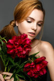 Beautiful girl with a bouquet of peonies. Model with a gentle make-up. Beauty face. Stock Photos