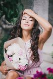 Beautiful girl with a bouquet of peonies. Beautiful girl in a pink dress with a bouquet of peonies Royalty Free Stock Photos