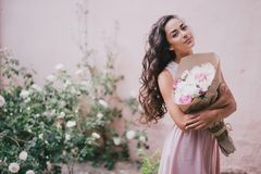 Beautiful girl with a bouquet of peonies. Beautiful girl in a pink dress with a bouquet of peonies Stock Photos