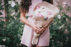 Beautiful girl with a bouquet of peonies. Beautiful girl in a pink dress with a bouquet of peonies Stock Photo