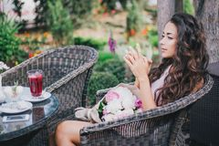 Beautiful girl with a bouquet of peonies sitting in a restaurant. Drinking berry tea Royalty Free Stock Photos