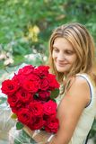 Beautiful girl with a bouquet of red roses royalty free stock photography