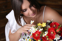 Beautiful girl and bouquet of  wildflowers. A young beautiful girl leaned over bouquet of flowers. Brunette girl in white dress Royalty Free Stock Photos