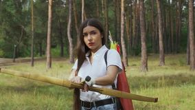 Beautiful girl with bow aiming. Close up. Female archer aiming her bow on target. Female bowman shooting target with her bow and arrow stock footage