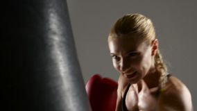 Beautiful girl boxer working with a punching bag. Gray studio. Beautiful girl boxer working with a punching bag, visible to the waist, makes the blows by hands stock video footage