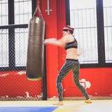 Beautiful girl boxing against punching bag (intentionally blurre Royalty Free Stock Photography