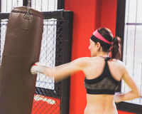 Beautiful girl boxing against punching bag (intentionally blurre Stock Photo