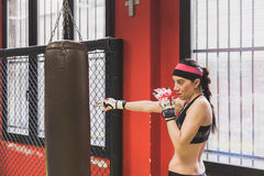Beautiful girl boxing against punching bag Royalty Free Stock Photography