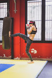 Beautiful girl boxing against punching bag Stock Images