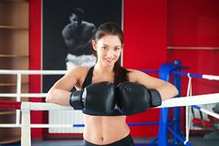 Beautiful girl in boxing gloves on ring royalty free stock photography