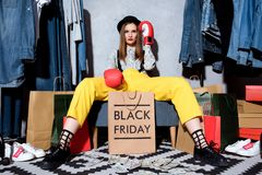 beautiful girl in boxing gloves with shopping bags and clothes around, black royalty free stock photo
