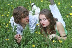 Beautiful girl and boy. On summer lawn with dandelions Royalty Free Stock Photos