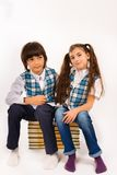 Beautiful girl and a boy sitting on a books Stock Photo