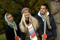 Beautiful girl and boyfriends. Beautiful girl in park pulling two boys by scarf, smiling Stock Images