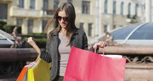 A beautiful girl with braces on her teeth shows bags with purchases turning around herself. The brunette in sunglasses shares impressions after shopping. 4K stock footage