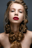 Beautiful girl with braids and gentle makeup. Nude. Beauty model with bright red lips. Stock Photography