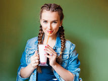 Beautiful girl with braids sitting in a cafe and drinking a milkshake, looling at the camera Royalty Free Stock Photography