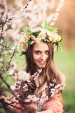 Beautiful girl among the branches of blossom cherry tree. Beautiful smiling girl dressed in wreath of flowers among the branches of blossom cherry tree Stock Photo