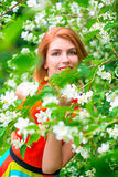 Beautiful girl in the branches of a flowering jasmine Royalty Free Stock Photography