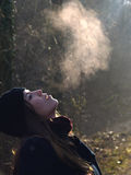 Beautiful girl breathing warm air. During a cold autumn morning stock photography